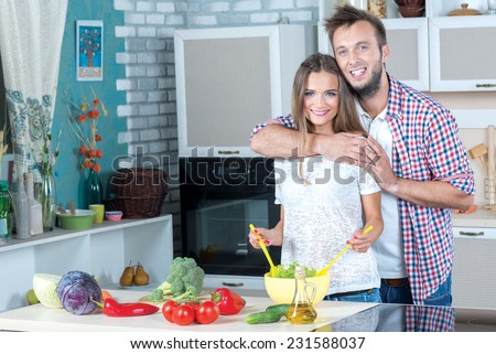Good emotions while cooking. Beautiful pair is standing on the kitchen is making healthy food on the kitchen. Both are smiling, while food looks delicious - stock photo