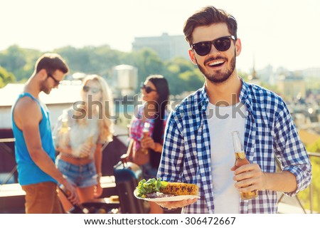Good food with best friends. Smiling young man holding bottle with beer and plate with food while three people barbecuing in the background - stock photo