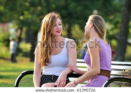 good friends having a heart to heart talk out on a park bench - stock photo