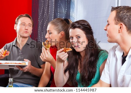 Good friends sitting together having a good time and some tasty pizza for lunch, focus on one woman - stock photo