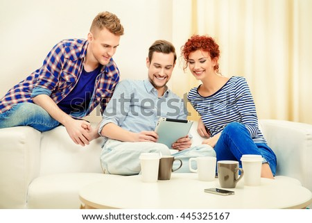 Good friends spending time together surfing in the Internet with a digital tablet. Weekend with friends.  - stock photo