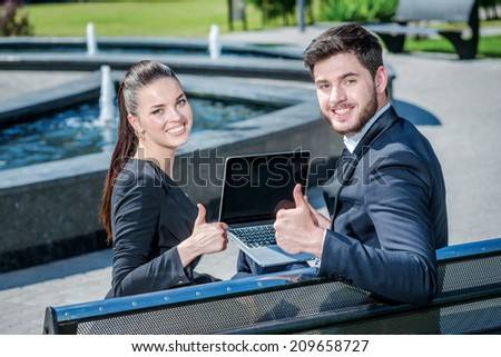 Good job. Confident businessman and successful business woman sitting on a bench and look back and smiling at the camera. - stock photo
