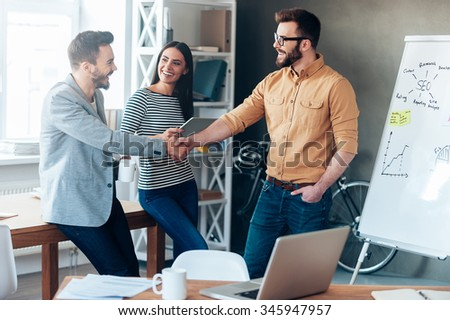 Good job! Confident young man standing near whiteboard and shaking hand to his colleague while young woman standing near them and smiling - stock photo