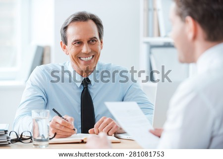 Good job! Two business people sitting in front of each other in the office while discussing something - stock photo