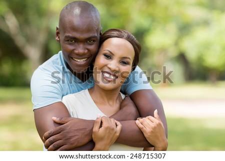 good looking african man hugging girlfriend outdoors - stock photo