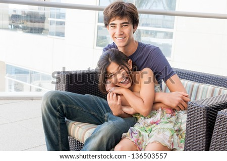 Good looking and loving Brother and Sister sit together on a patio at a luxury hotel - stock photo