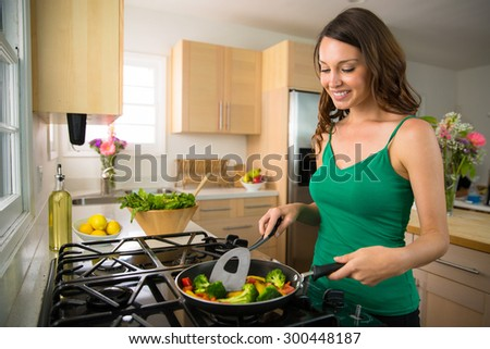 Good looking beautiful woman female vegan vegetarian prepares a low calorie dinner - stock photo