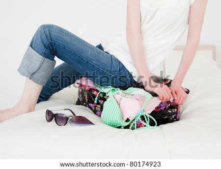Good looking blonde female trying to close her suitcase in her bedroom in her apartment - stock photo