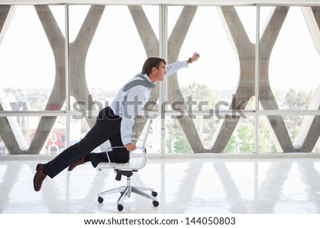 Good looking Business man Flying on a chair as if to be superman - stock photo