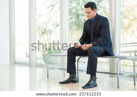 Good-looking businessman sitting on a bench and checking email on a tablet computer - stock photo
