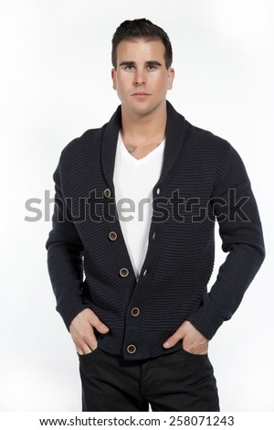 Good looking caucasian athletic male model wearing a trendy buttown down sweater, black pants and a white t-shirt posing in a studio on a white background while looking at the camera with his hands in - stock photo