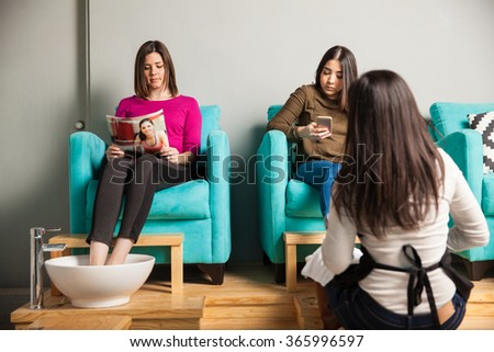 Good looking couple of women passing time and waiting at a nail salon for a pedicure - stock photo
