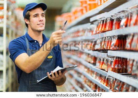 good looking hardware store worker counting stock - stock photo