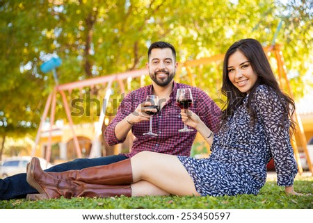 Good looking Hispanic couple drinking some wine while relaxing together at a park - stock photo