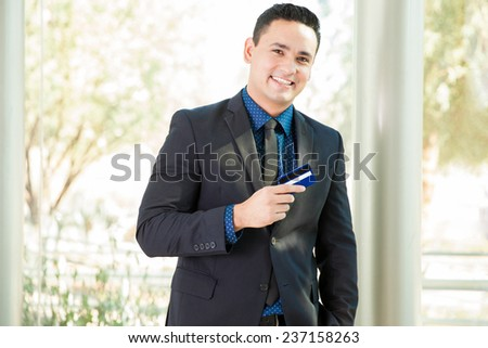 Good-looking Hispanic man in a suit holding a credit card and smiling - stock photo
