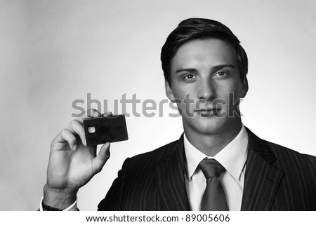 good looking male holding up a blank bank card - stock photo