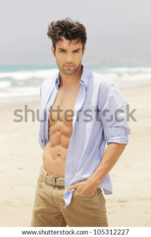 Good-looking man on beach with open shirt - stock photo