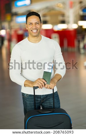 good looking man traveling holding passport and boarding pass at airport - stock photo