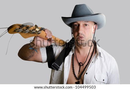 Good looking man wearing a cowboy hat and an open shirt - stock photo
