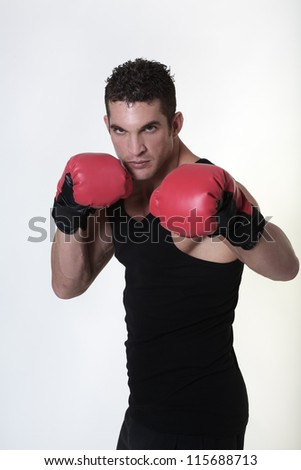 good looking man wearing boxing gloves and working out - stock photo