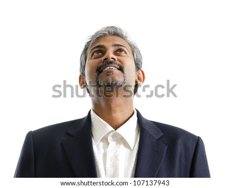 Good looking mature Asian Indian male with business suit looking up, isolated on white background - stock photo