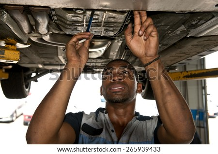 Good Looking Mechanic Checking Out Vehicle - stock photo
