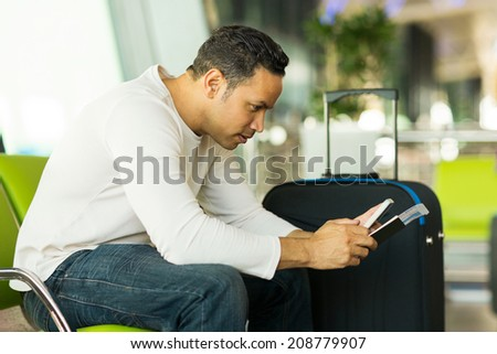 good looking mid age man using smart phone at airport - stock photo