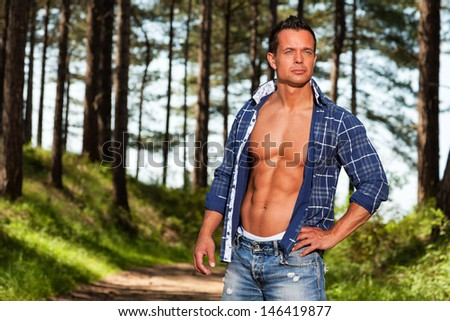 Good looking muscled fitness man with blue lumberjack shirt in forest. - stock photo