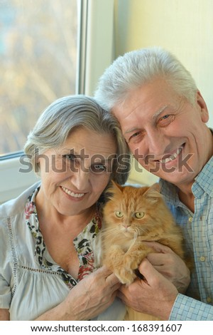 Good-looking older couple sitting at home with cat - stock photo