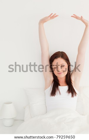 Good looking red-haired female stretching in her bed - stock photo