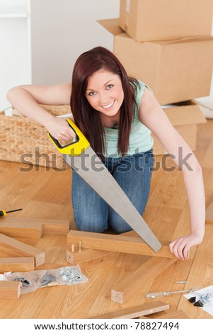 Good looking red-haired woman using a saw for diy at home - stock photo