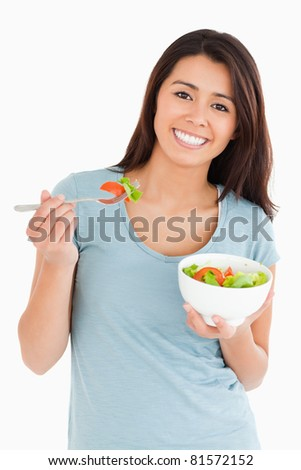 Good looking woman eating a bowl of salad while standing against a white background - stock photo
