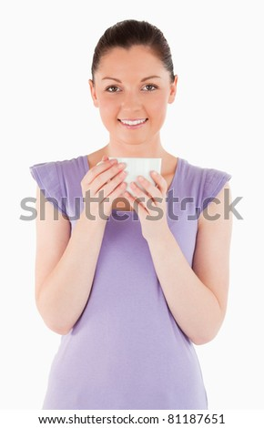 Good looking woman enjoying a cup of coffee while standing against a white background - stock photo