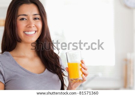 Good looking woman holding a glass of orange juice while standing in the kitchen - stock photo