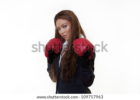 good looking woman in a suit wearing boxing gloves - stock photo