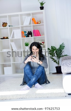 Good looking woman listening to music with headphones while sitting on a carpet in the living room - stock photo
