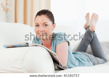 Good looking woman reading a magazine while lying on a sofa in the living room - stock photo