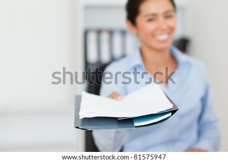 Good looking woman showing a sheet of paper to the camera at the office - stock photo
