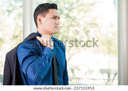 Good-looking young businessman taking a break from work and carrying his jacket from his shoulder - stock photo