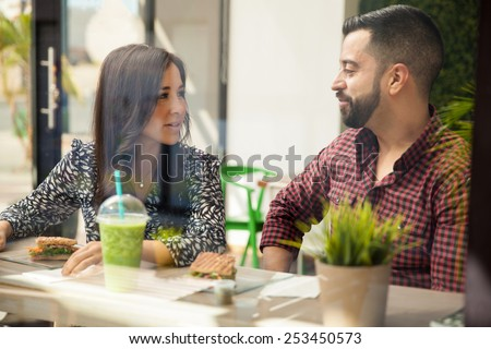 Good looking young couple having lunch together at a sandwich shop - stock photo