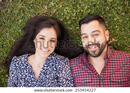 Good looking young Hispanic couple lying on the grass and relaxing in a park - stock photo