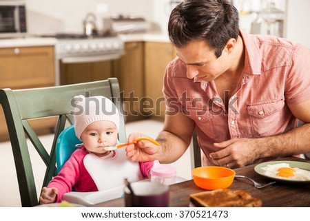 Good looking young man eating breakfast and feeding her baby girl at home - stock photo