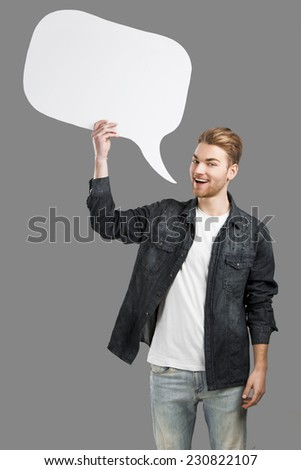 Good looking young man holding and talking to a speack balloon - stock photo