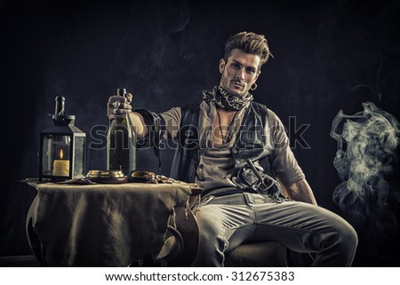 Good Looking Young Man in Pirate Fashion Outfit Sitting next to Table with Candle Lamp, Compass, Gold - stock photo