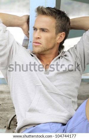 Good-looking young man outdoors looking off to the left in casual clothing - stock photo