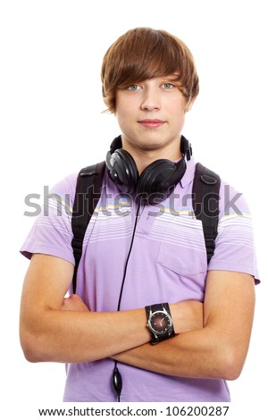 Good-looking young man standing cross-armed and looking at camera - stock photo