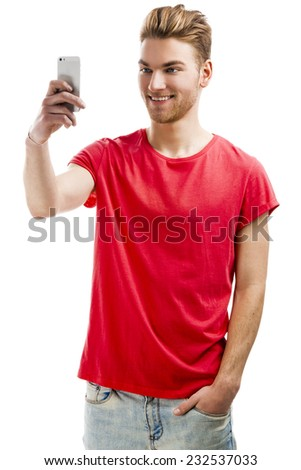 Good looking young man taking a selfie with his cell phone - stock photo