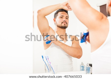 Good looking young man with a beard putting on some deodorant in front of a mirror in a bathroom - stock photo