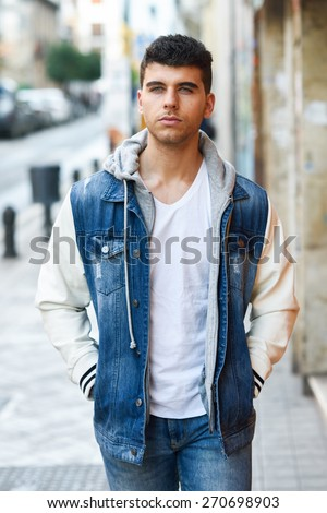 Good looking young man with blue eyes in the street. Model of fashion in urban background wearing white t-shirt, jeans and blue jacket - stock photo