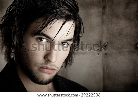 Good looking  young man with modern HairStyle over a grunge wall background - stock photo